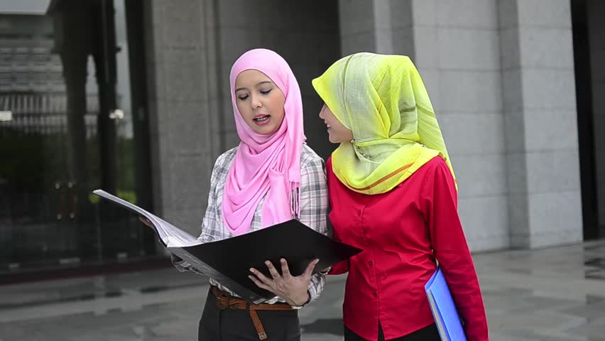 Portrait of pretty young Muslim woman sharing idea while hold file and smile