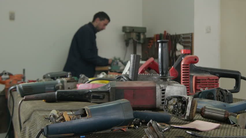 Broken Open Electric Devices On The Table In Focus Young Serviceman Fixing Rotor Of Apparatus