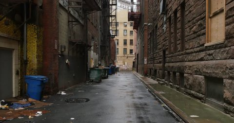 A daytime overcast establishing shot of an empty alley in a big city.