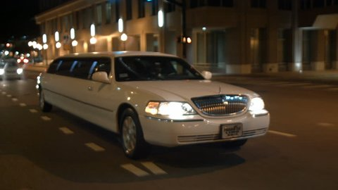 stretched limo driving urban city streets night