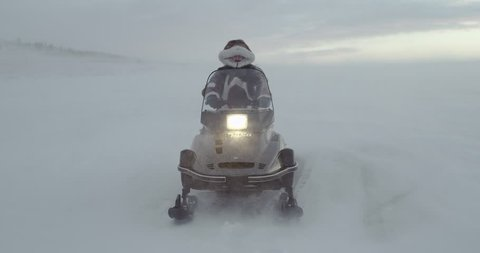 An adventurer  dressed in reindeer coat with fur hood looks away on a snowmobile at blizzard. Arctic expedition 2016. 4k shot , slow motion.