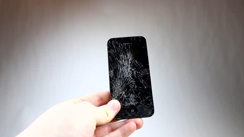 KAUNAS, LITHUANIA - DECEMBER 28, 2016: Screen broken smartphone. Broken Iphone 4. Cracking mobile phone with hammer   Shutterstock HD Video #22651282