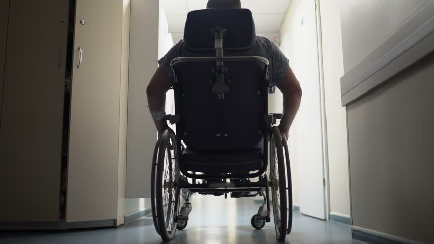 Rear view of disabled man pushes himself in wheelchair down hospital corridor
