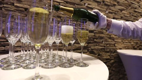 The waiter pours champagne into glasses, champagne glasses on the buffet table, the hall of the restaurant or hotel, the waiter's hand in a white glove with a bottle of champagne, indoor, close-up