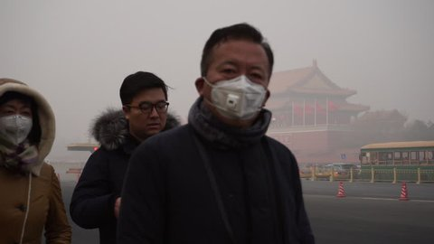Jan.1,2017-Beijing,China: People walk past Tiananmen Rostrum, wearing mask to prevent breathing in the toxic air.  On the first day of 2017, Beijing suffered its first severe haze of the new year.