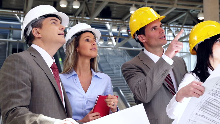 Group of professional engineers and architects in the industrial building.