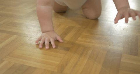 Close-up tracking shot of baby's hands and feet when crawling on wooden floor.
