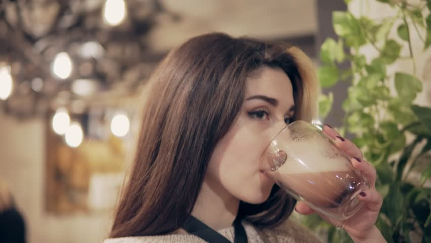 Beautiful young brunette woman drinking hot cacao in decorated cafe | Shutterstock HD Video #22727392