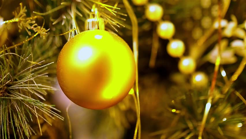 close up of gold christmas balls hanging on artificial fir flashing yellow lights christmas - Gold Christmas Tree Lights