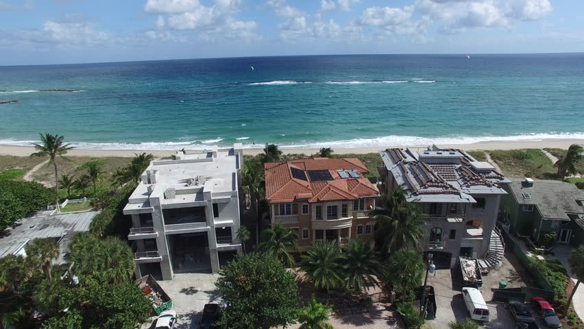 Drone flight to home construction on beach. Referencing building near ocean during sea level rise.