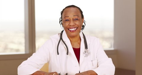 An older black doctor happily giving medical advice in a video chat. An elderly African American medical expert cheerfully speaking to the camera. 4k