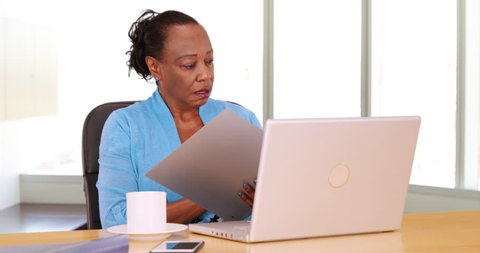 An African American businesswoman uses her laptop at her desk. A black woman uses her computer in her office. 4k