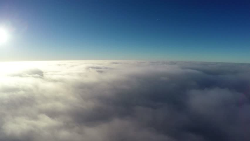 Aerial bird-eye view flying steady altitude above thick clouds towards bright sun beautiful contrast showing crisp blue sky the darker atmosphere above bright sunshine and slowly moving clouds below