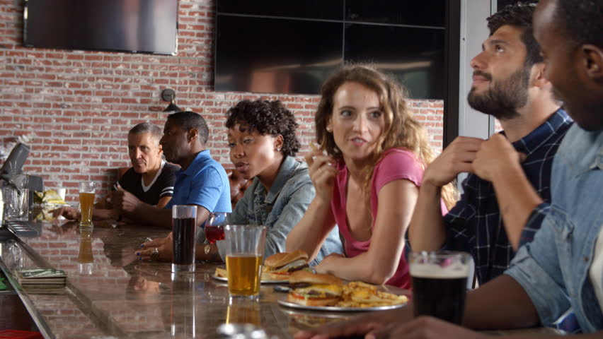 Group Of Friends Watching Game In Sports Bar On Screens | Shutterstock HD Video #22781782