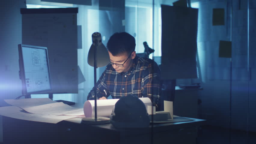Young Capable Architectural Engineer Working Late Hours in His Office. Office is Dark Only His Table Light is On. Various Plans and Blueprints Lying on the Table. He Writes Down His Calculations. #22781872