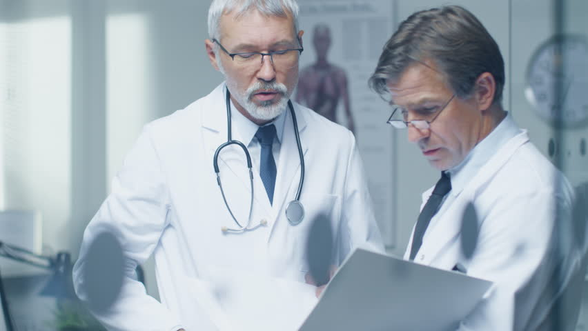 Two Specialist Doctors Discussing Patient's Log. Both are Senior and Experienced. Their Office Looks Modern and Respectable. Shot on RED Cinema Camera in 4K (UHD). | Shutterstock HD Video #22782502