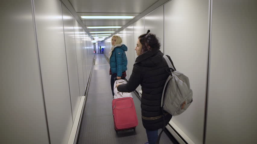 Airport. Two young women running on your flight. Blonde girl with a suitcase in a hurry to pass through the pipe to the plane. Brunette with a backpack on his shoulders in a great mood. | Shutterstock HD Video #22799131