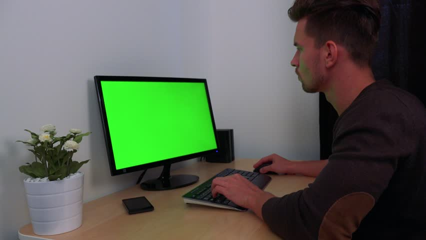A young, handsome man types on a computer with a green screen | Shutterstock HD Video #22850380