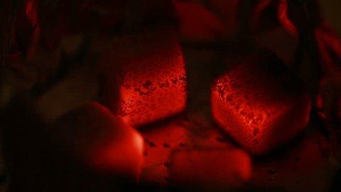 Hot coals in the hookah bowl in darkness closeup