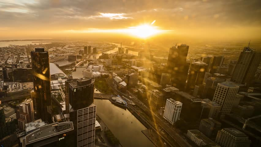 Time lapse of an aerial view of Melbourne City Center during sunset with beautiful sun burst emerged between fast moving clouds. Digital zoom out with pan from right to left. | Shutterstock HD Video #22867252