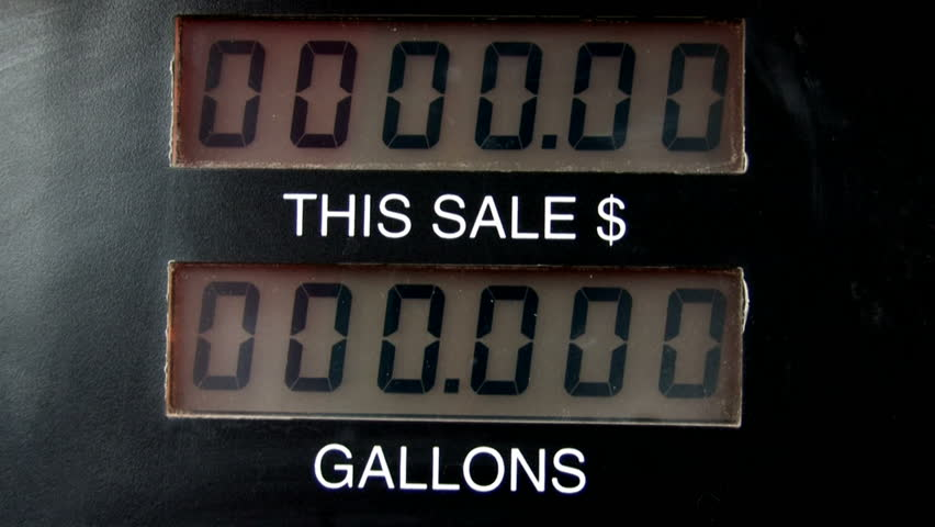 Gas pump showing dollars and gallons going up. Tops out at $75 when pump automatically turns off for credit card purchase. Time lapse fast motion.Gas company price gouging. High cost of driving.