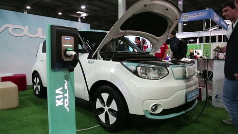 UKRAINE, KIEV, JUNE 10, 2016: People at exhibition of electric cars. KIA Soul EV electromobile is being charged. Car with openned bonnet