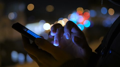 Close-up shot of woman hands with smartphone in the city at night. Technology, winter and holiday concept