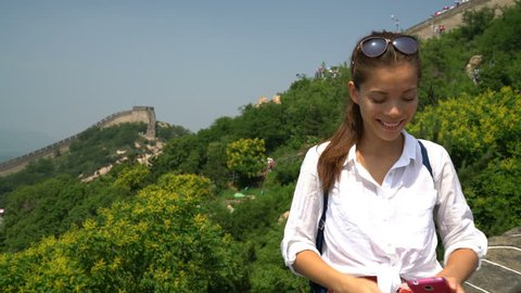 Great Wall of China. Woman tourist taking selfie photo at famous Badaling during travel holidays at Chinese tourist destination. Woman tourist taking picture using smart phone during Asia vacation.