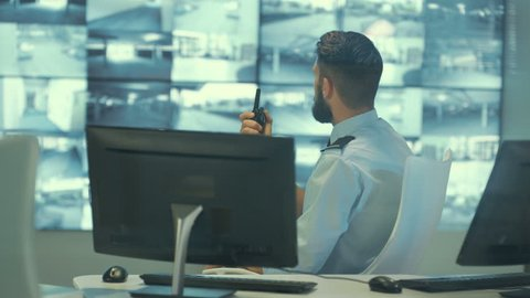 4K Security team watching CCTV video screens in observation control room Dec 2016-UK