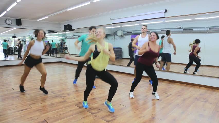Smiling men and ladies dancing zumba at lesson