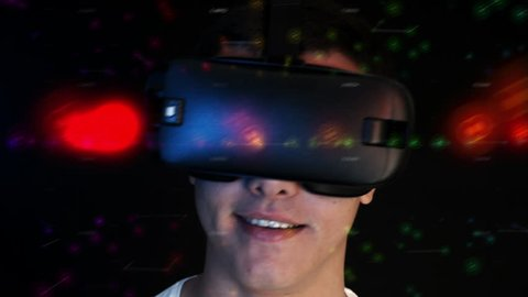 Smiling young man wearing VR Headset experiencing virtual reality. 3D objects flying around head.