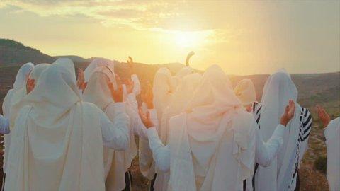 Jewish men praying With tefillin and shofar in sunset