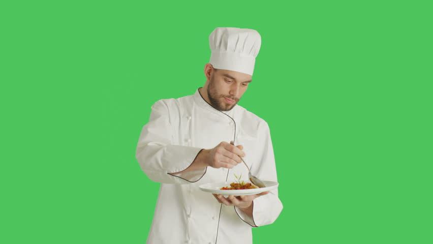 Mid Shot of a Handsome Chef Holding Plate With Dish Decorating Dish with a Spoon. Shot with Green Screen Background. Shot on RED Cinema Camera 4K (UHD).