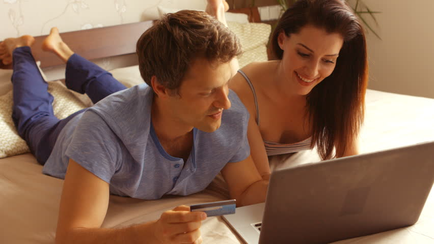Couple shopping online on laptop using credit card on bed in bedroom 4k | Shutterstock HD Video #22950262