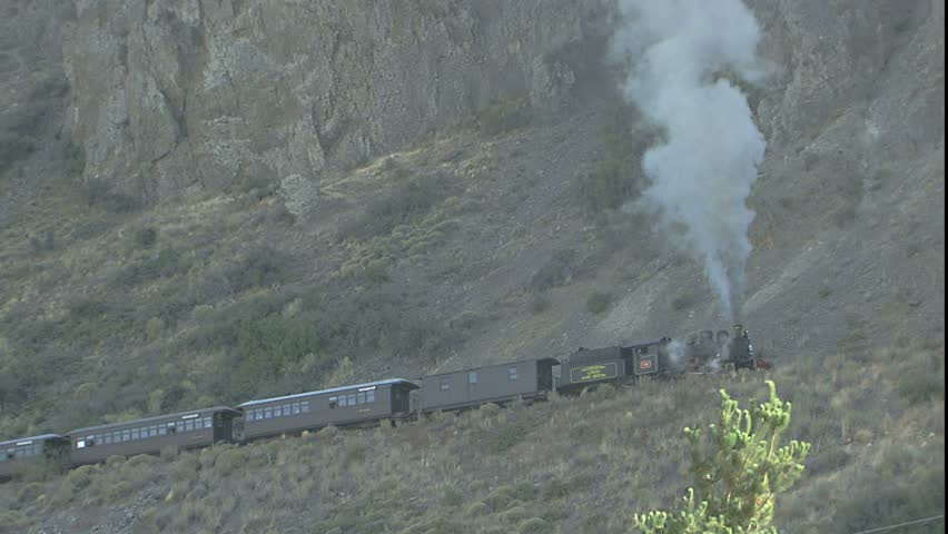 Steam Locomotive moves into Frame, scene is Engine comes into frame and traverses steep hill side belching smoke