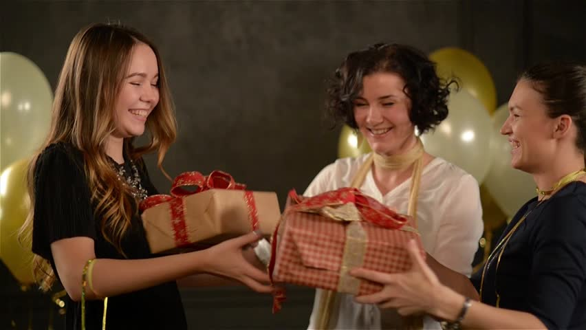 Two Excited Women Congratulate Their Friend Hugging Her and Giving a Presents. Birthday Girl Recieved Boxes with Gifts. Black Background with White and Golden Air Balloons.