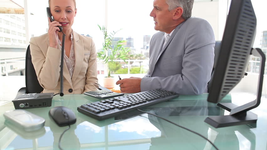Businessman talking to his colleague as she makes a phone call in an office | Shutterstock HD Video #2300042