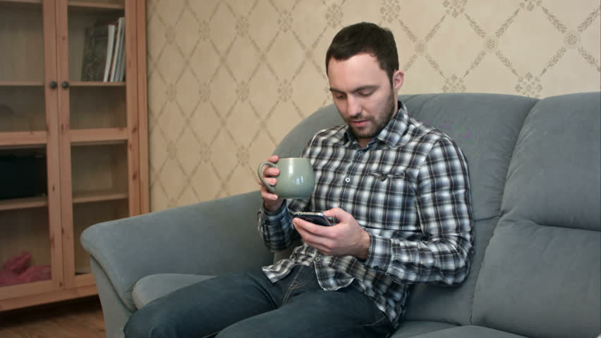 778aa5b5bc Young man with smartphone sitting on couch at home. F. By Fancy Studio. Stock  footage ID  23008672. Video clip ...