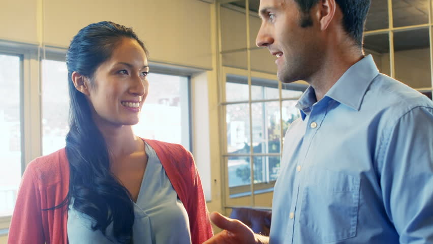 Male and female business executives interacting with each other in office | Shutterstock HD Video #23008942