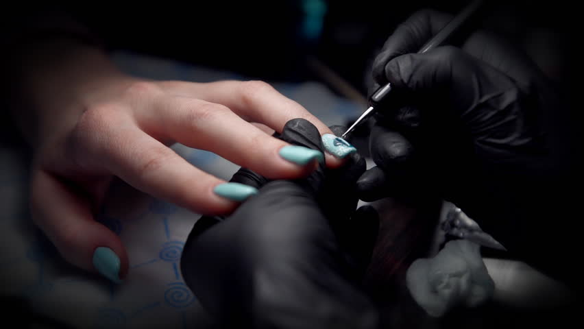 Manicurist In Black Gloves Makes A Beautiful Manicure On Layer Of Blue Nail Polish After