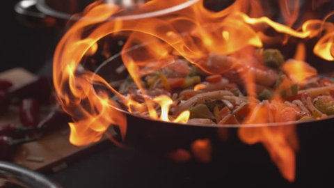 Stir fry into flaming pan in super slow motion, shot on 4K