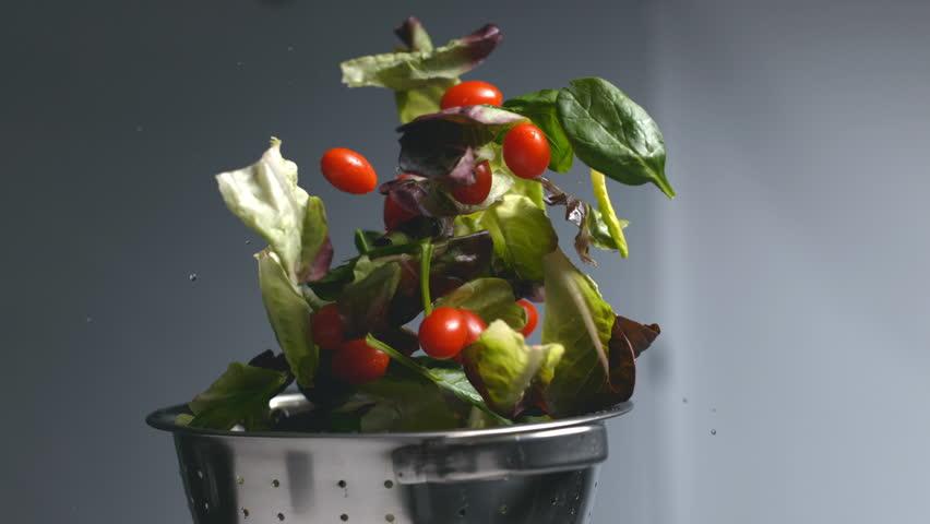 Salad flying out of colander in super slow motion, shot on Phantom Flex 4K