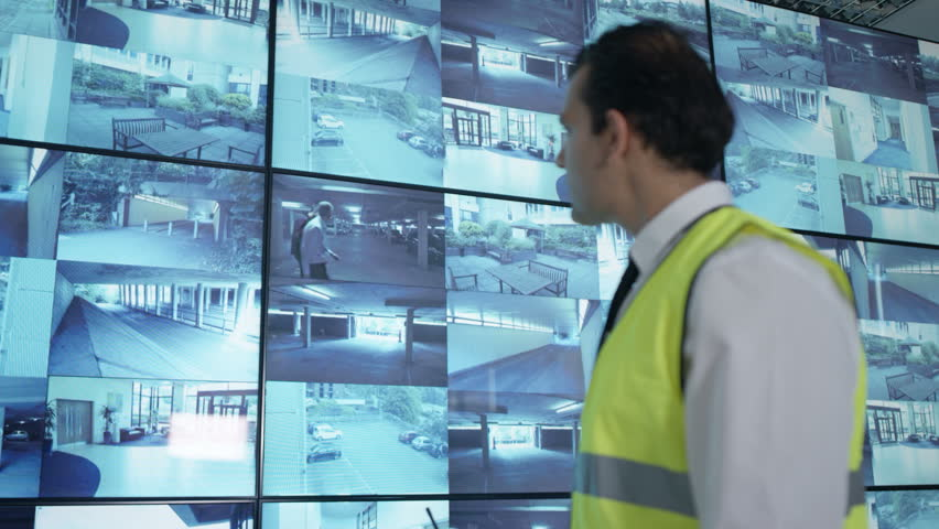 4K Security officer watching CCTV video screens & talking on radio Dec 2016-UK | Shutterstock HD Video #23015872