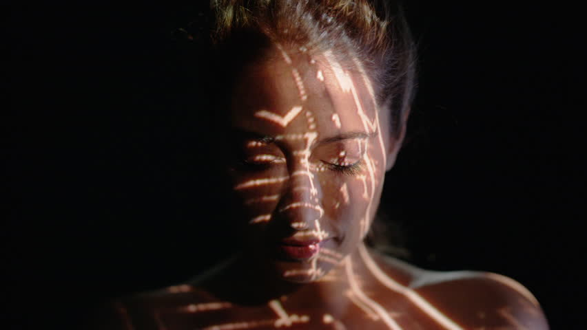 4K Light projected onto woman's face indicating brain activity or migraine Dec 2016-UK