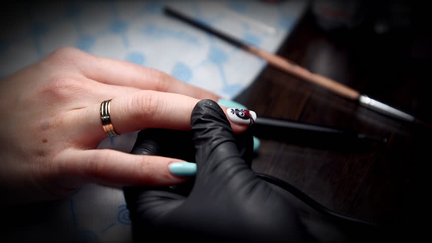 Manicurist In Black Gloves Gets A Top Coating On The Nail With Drawing Of Penguin