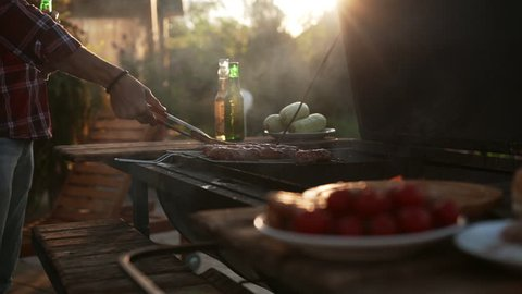 Close up view of two men making barbecue outdoors drinking beer talking smiling in slowmotion. Close up