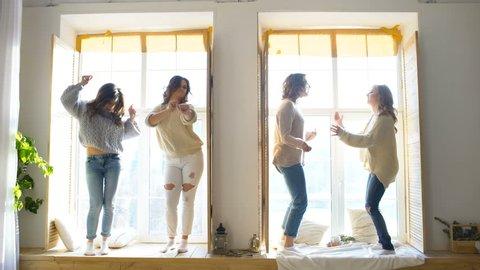 Happy and beautiful girlfriends dance on window having fun and joy in bedroom