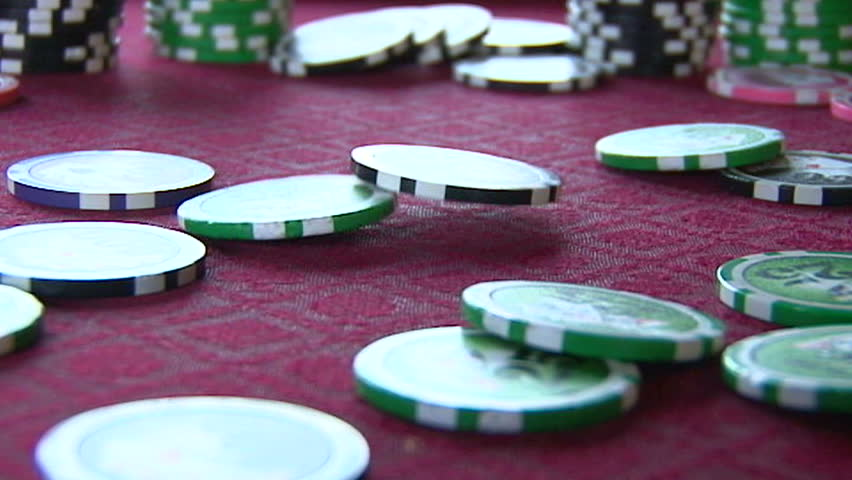 Slow Motion of poker chips falling on card table in casino close up.