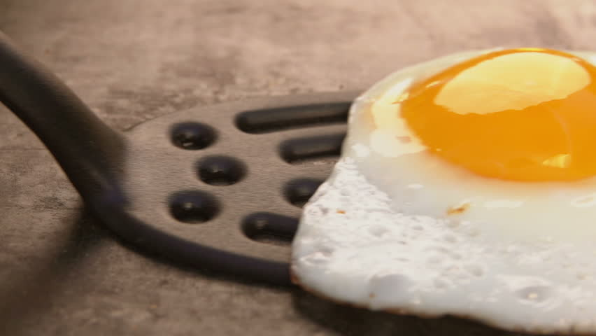 Cook picks up fried egg with a spatula grill