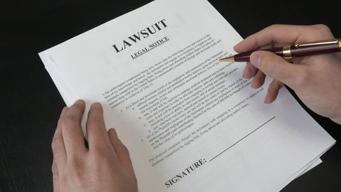 Signing a Lawsuit document. Closeup on the legal paper.
